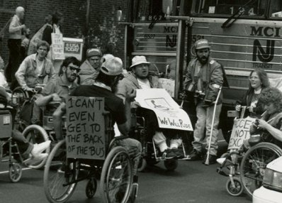 """""""I can't even get to the back of the bus."""" ADAPT activists protesting for accessible transportation, Philadelphia, 1990. [Smithsonian National Museum of American History]"""